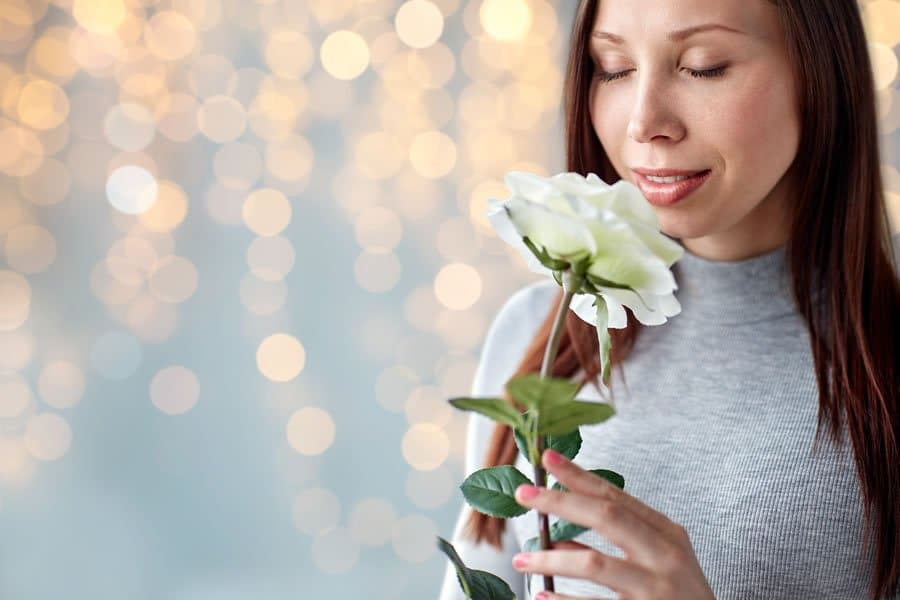 Woman sniffing a flower, suffering from allergies