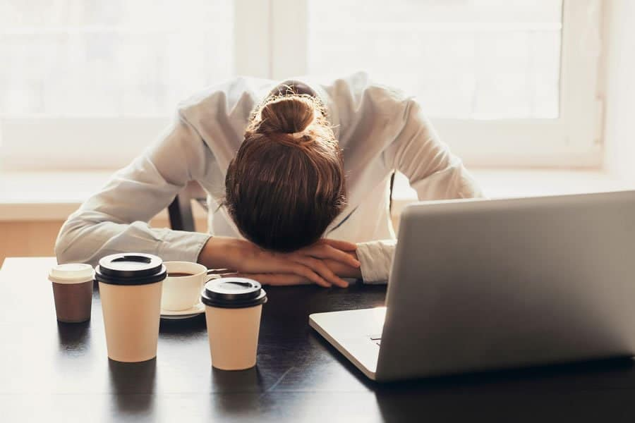Young person at work suffering fromChronic Fatigue Syndrome Symptoms
