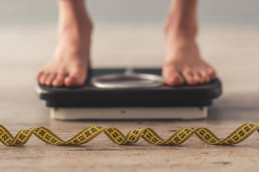 A person standing on a scale, after having received medically supervised accelerated diet