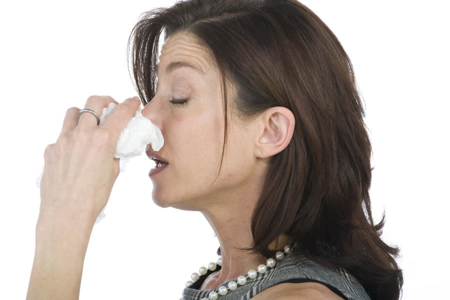 Woman holding her nose. The connection between Allergies and Alzheimer