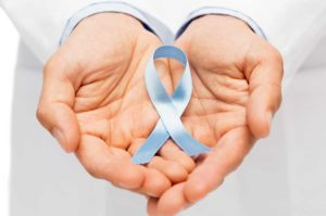 A man holding a blue ribbon in his hands, symbolizing prostate cancer