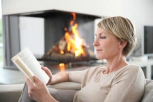 A woman reading by the fire. Ozone therapy restored her vision.