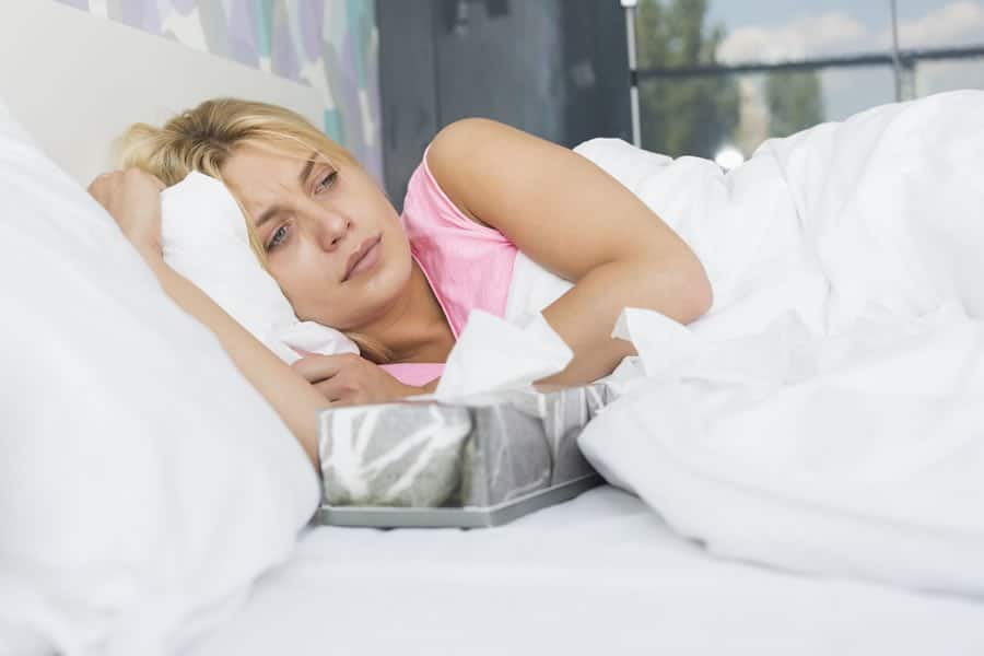 Woman in bed, suffering.illnesses and diseases that respond to ozone therapy
