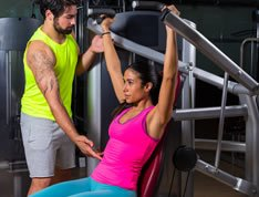 Woman working out at the gym with the help of a trainer