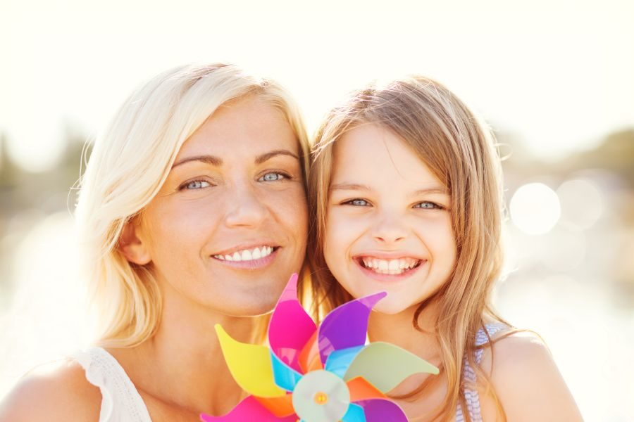 Happy mother and child girl with pinwheel toy. Denise's success story