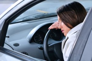 Chronically fatigued woman sleeping on the car's wheel because of Lyme disease