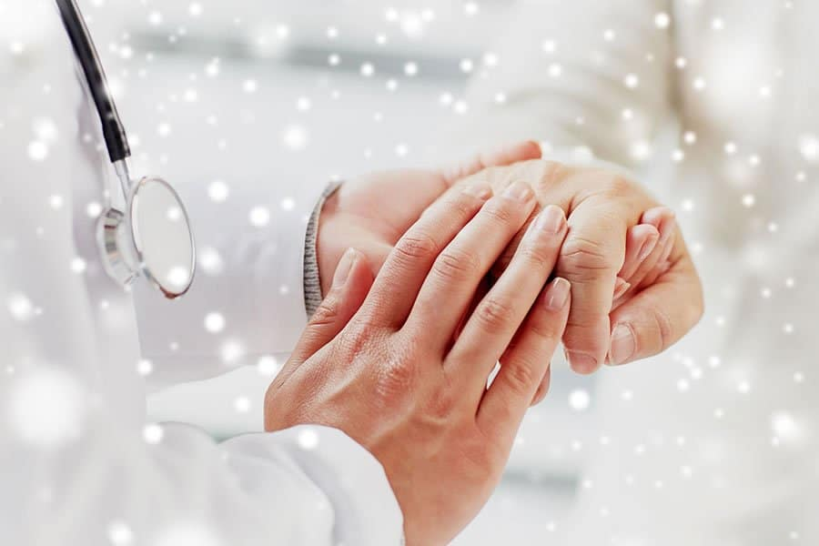 A patient holding the doctor's hand as a sign of gratitude
