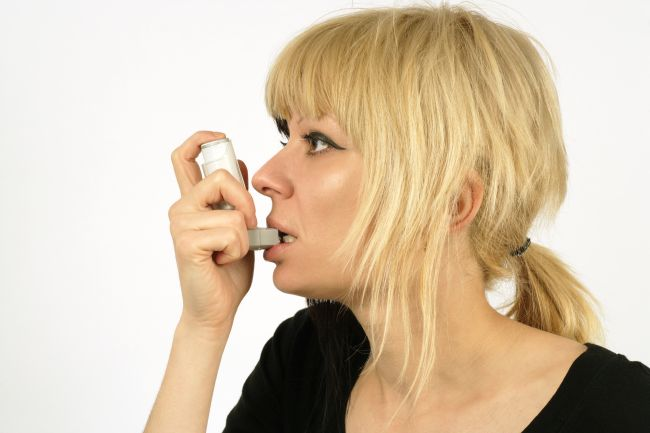 Asthmatic patient with an inhaler in her mouth