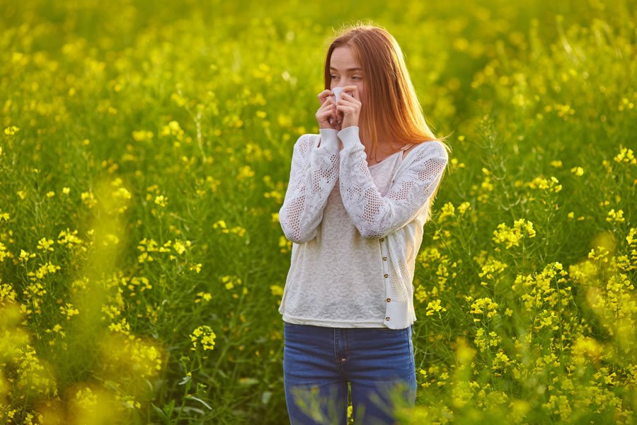 Woman in a field, suffering from Seasonal Allergies (Hay Fever)
