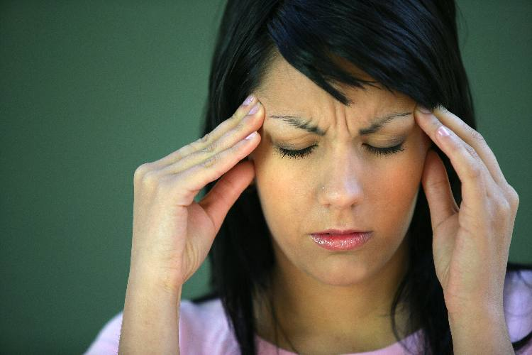Woman grasping head with a lyme disease headaches showing what it feel like